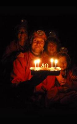 Homme qui souffle ses bougies dans une grotte avec sa famille